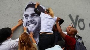 Unos manifestantes colocan un retrato del diputado Juan Requesens, en una pared de Caracas.