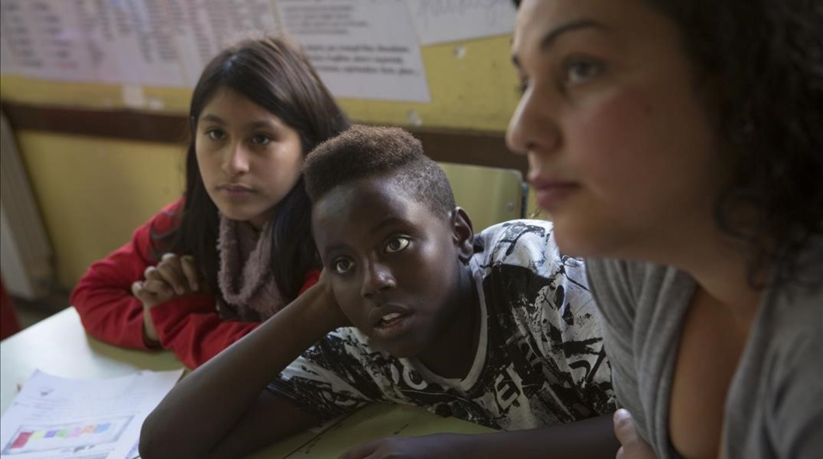 Dos alumnos y una madre durante una clase en el colegio Joaquim Ruyra de L'Hospitalet de Llobregat, el pasado noviembre.