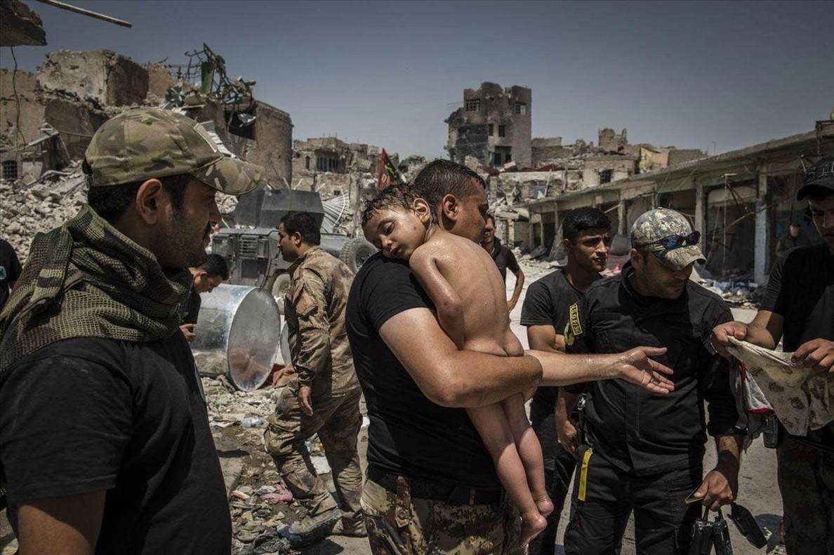 Un niño es cuidado por soldados de las Fuerzas Especiales iraquís, en Mosul.