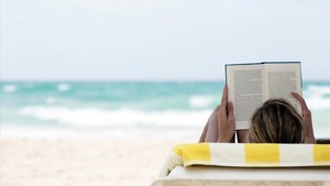 Un trabajador leyendo un libro disfrutando de las vacaciones.
