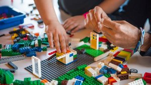 Menores juegan con piezas de construcción de Lego.