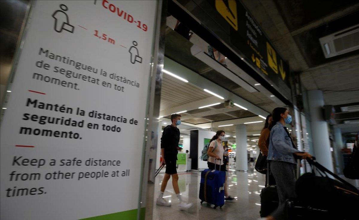 Pasajeros a su llegada al aeropuerto de Palma de Mallorca pasan frente a un cartel alusivo al coronavirus.