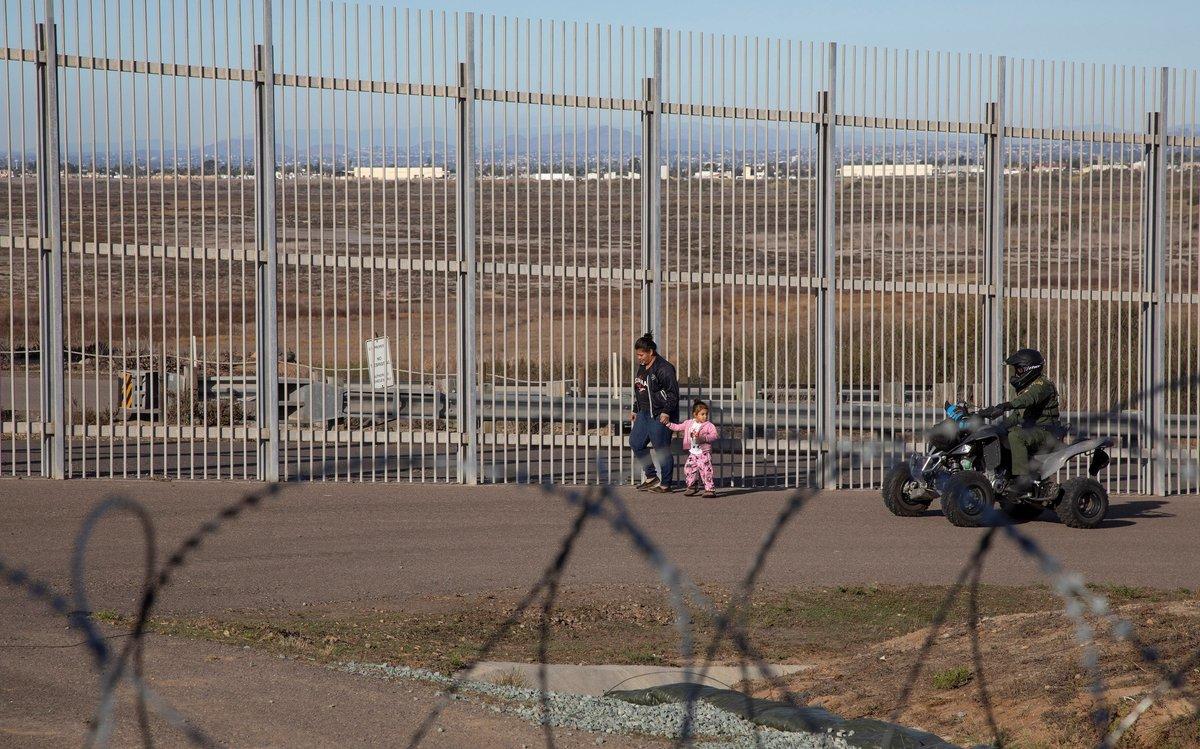 Una mujer migrante es detenida por la policia estadounidenseen el muro fronterizo de la ciudad de Tijuanaen Baja California,Mexico.EFE Alonso Rochin
