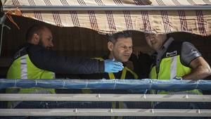 Agentes de la policía científica,en el balcón desde el quese intentósuicidarun hombre tras degollar a su hija.
