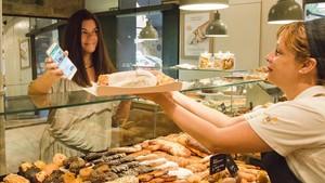 Eva Jorge, la ideóloga de weSAVEeat, muestra la 'app' en su móvil en el mostrador de una panadería SantaGloria.El lote que le ofrecen cuesta 3 euros.