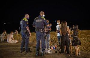 Agentes de policía advierten a jóvenes que están bebiendo en la playa de la Nova Icària, a las 23.40 horas del 23 de julio.