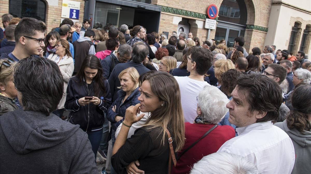 Ciudadanos esperando pacientemente la resolución de los problemas informáticos en Figueres.