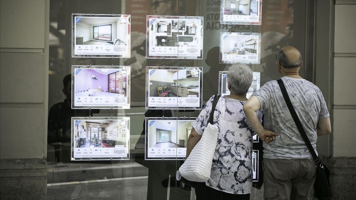 Un pareja consulta la información de una agencia inmobiliaria de Barcelona.