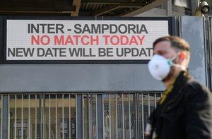 Un hombre pasa con una mascarilla frente al estadio de San Siro, donde se ha suspendido el Inter-Sampdoria.