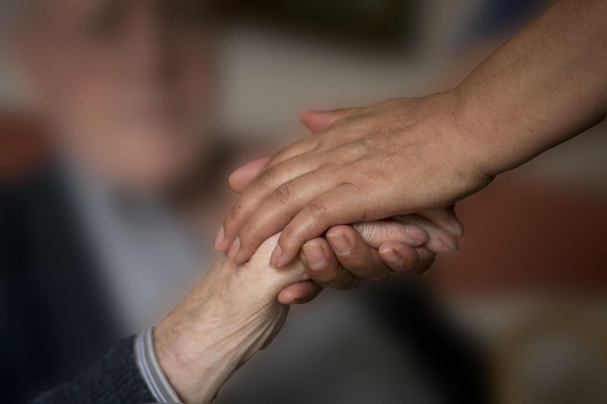 Un cuidador coge la mano de un enfermo de alzhéimer.