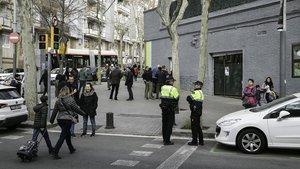 Dos agentes de la Guardia Urbana custodian la entrada de los alumnos del Joan Roca de Guipúscoa, esta mañana