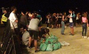 Jóvenes que asistieron al concierto de la playa delBogatell, recogiendo plásticos, el pasado viernes.