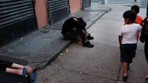 Unos niños caminan junto a dos heroinómanos por una calle del Bronx, uno de losbarrios de Nueva York más afectados por esta droga.