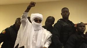 El expresidente del Chad Hissène Habré levanta elbrazo tras escuchar la sentencia a cadena perpetua.