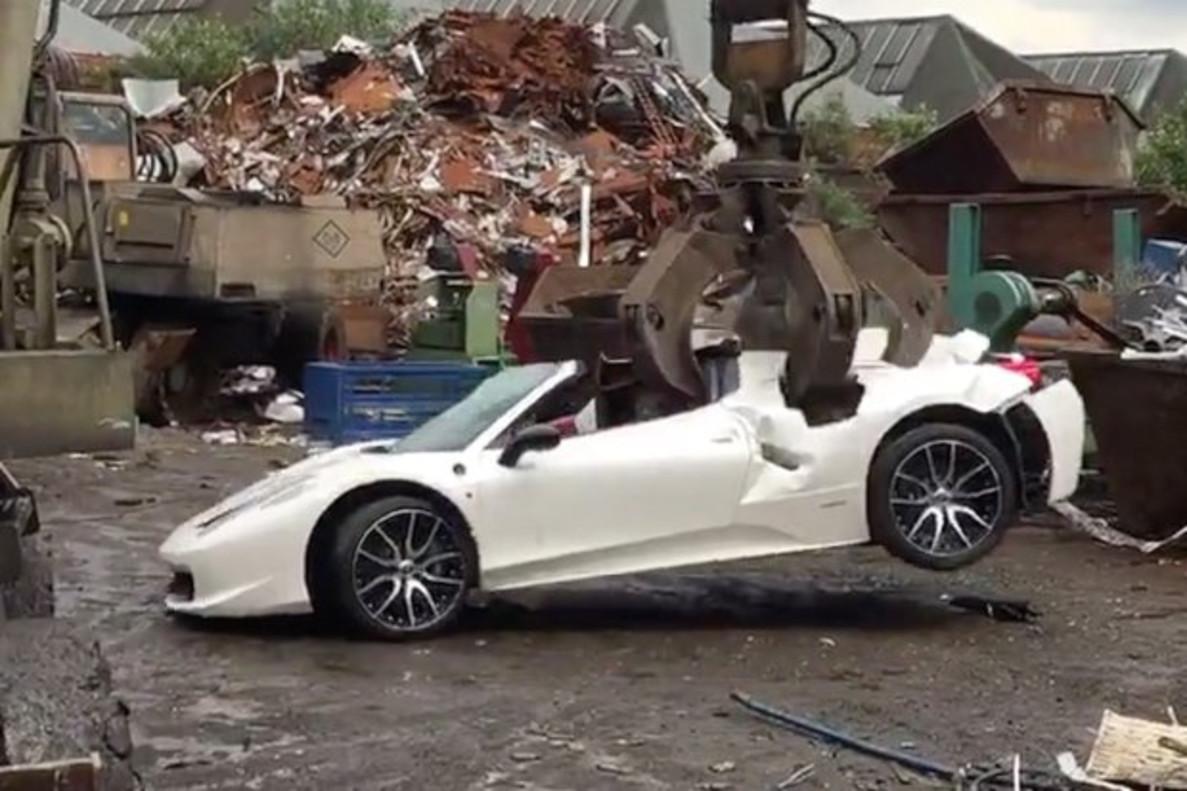 El Ferrari 458 Spider siendo destrozado por una grúa en un desguace.