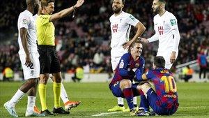 Griezmann levanta a Messi tras recibir el argentino una falta.