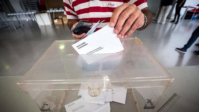 Un hombre introduce su voto en la urna.