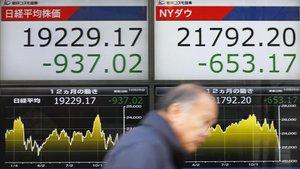 Un hombre pasa ante un cartel que exhibe las pérdidas del índice Nikkei, a la izquierda, y del Dow Jones, en una firma de valores en Tokio
