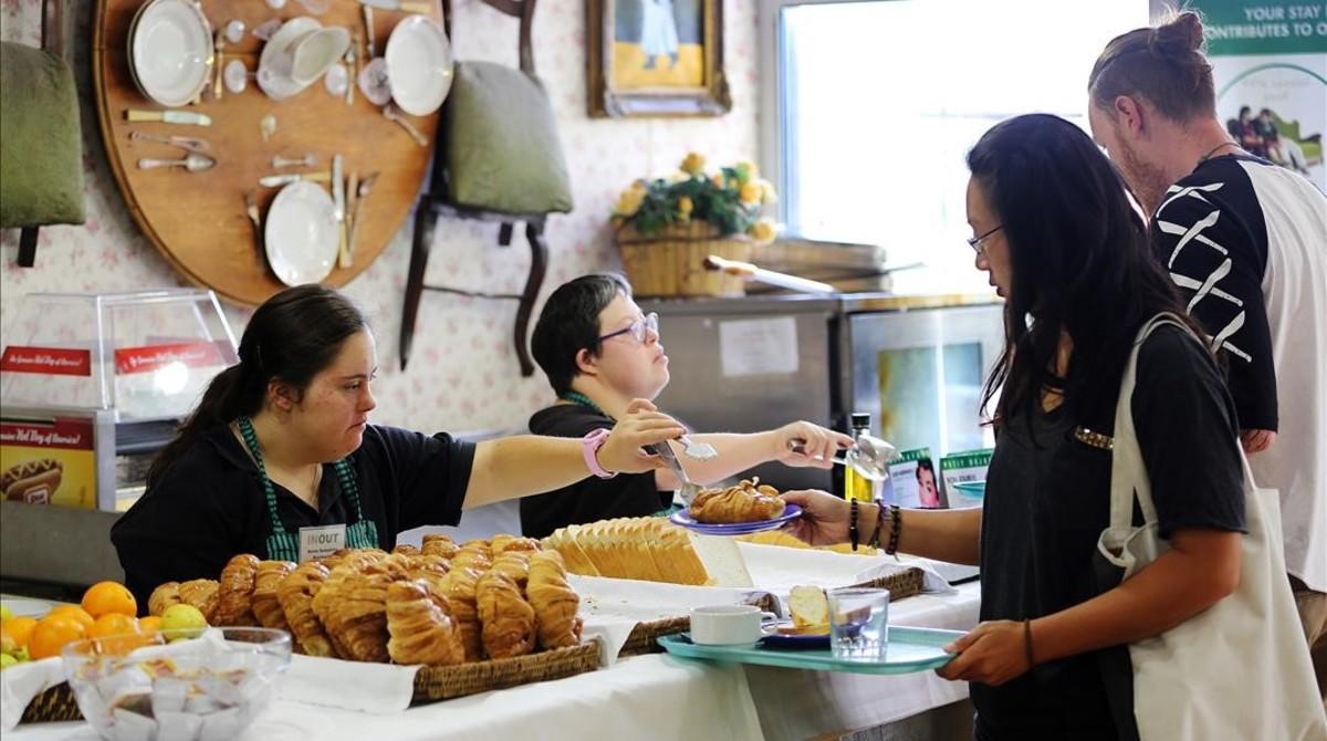 Dos jóvenes con síndrome de Down atienden a los clientes de una panadería en Barcelona.