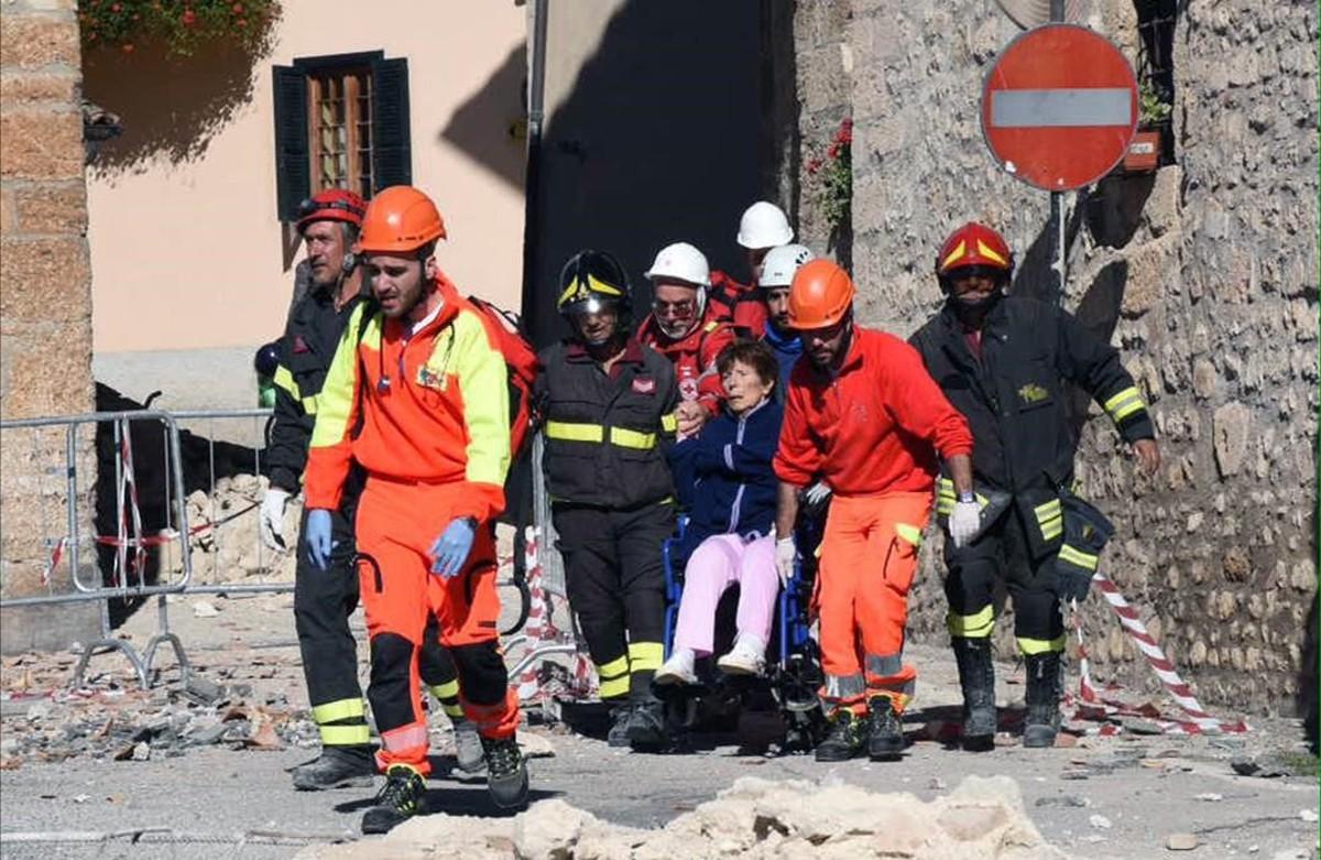 Los bombaros ayudan a una vecina en silla de ruedas a abandonar la localidad italiana de Norcia, afectada por los terremotos.