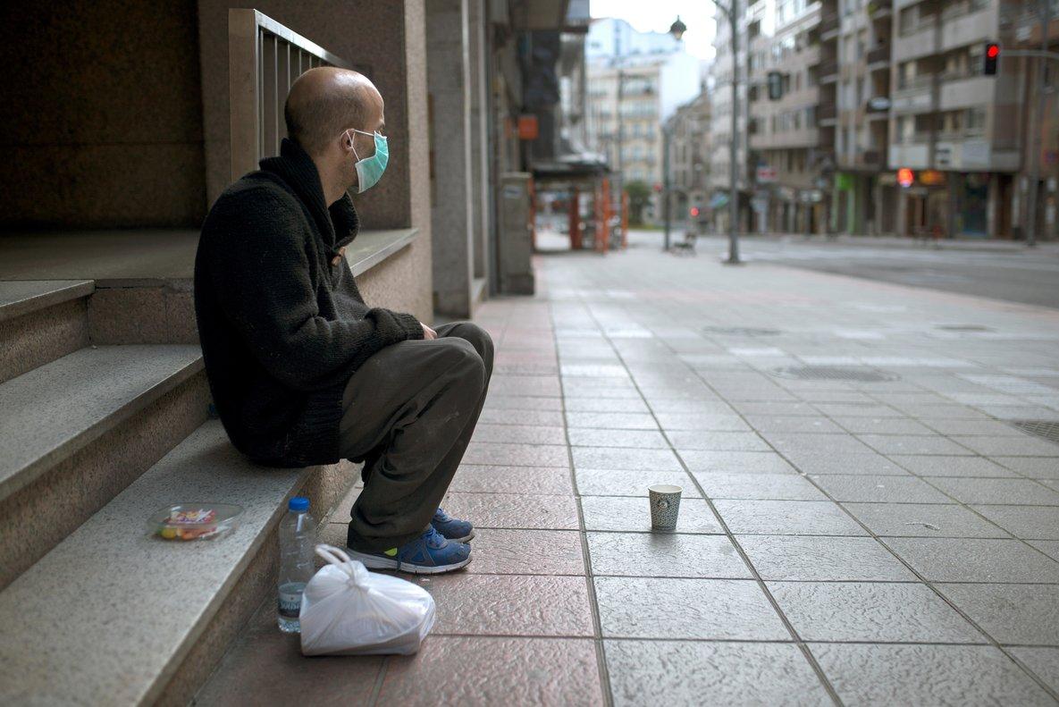 GRAF8292. OURENSE, 17/03/2020.- Un hombre sin hogar con una mascarilla sanitaria permanece sentado en una céntrica calle de Ourense, Galicia, comunidad donde los infectados con coronavirus ascienden a 285. EFE//Brais Lorenzo
