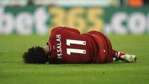Salah tendido en el campo de juego tras sufrir el golpe en la cabeza.