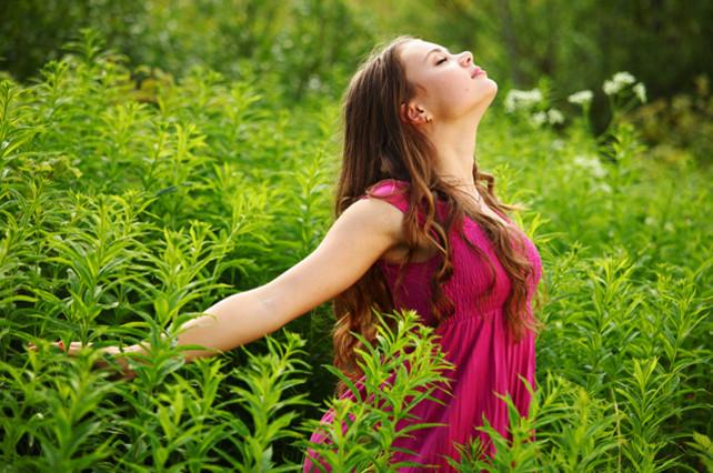 Mujer sintiendo plenitud con los brazos abiertos.