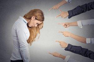Mujer sintiendo culpa ante los dedos que la señalan.
