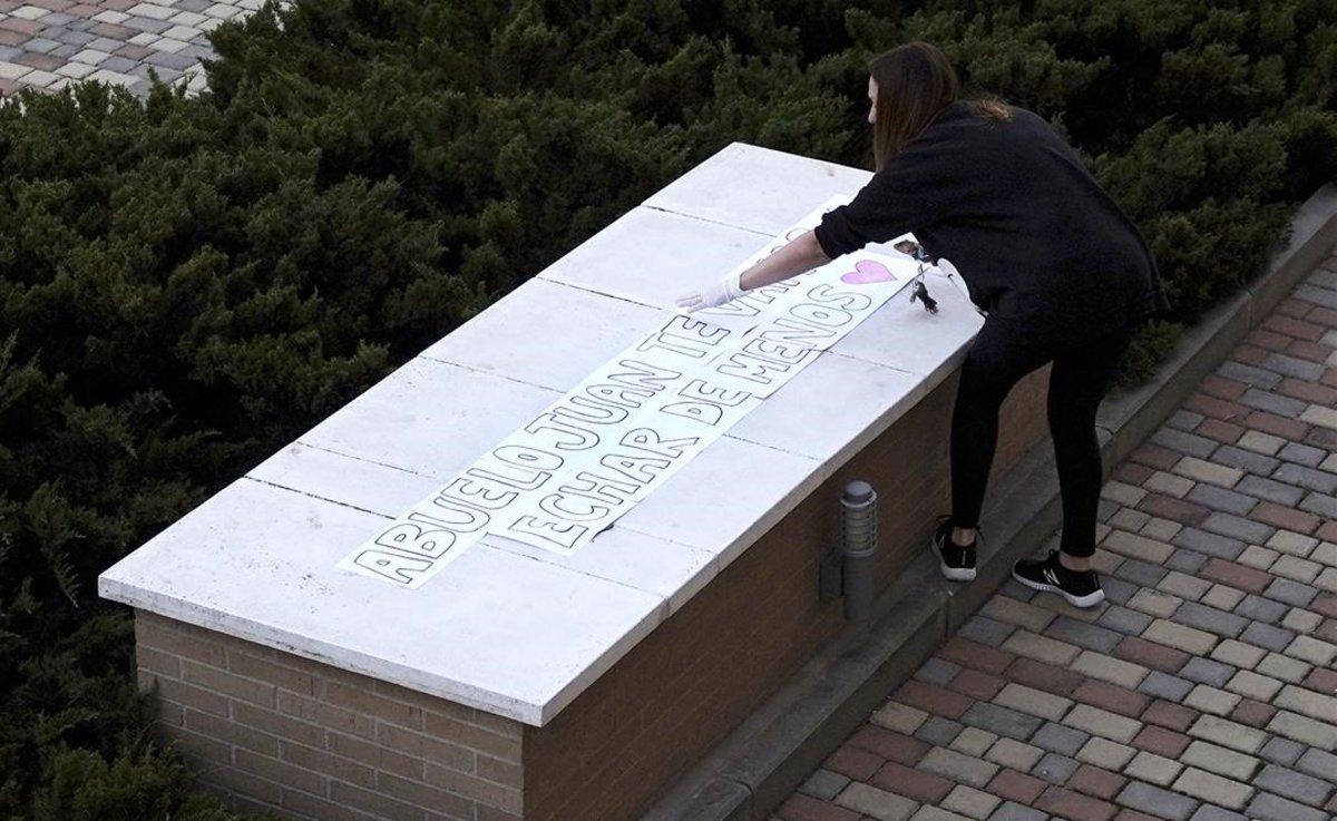 Una vecina de Boadilla del Monte (Madrid) pega una pancarta para honrar la muerte del abuelo paterno de su hijo