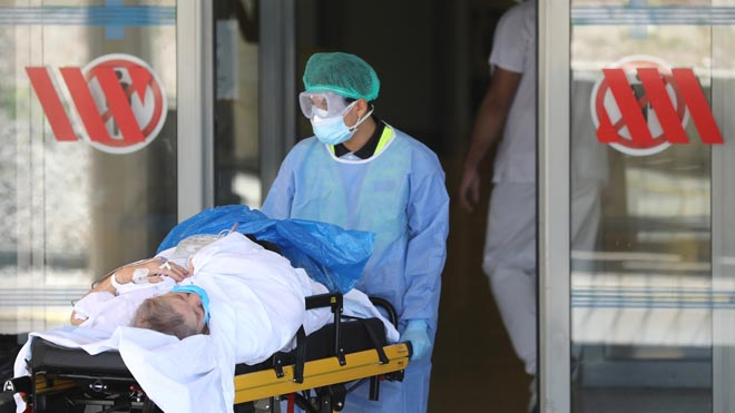 Primer lunes laborable de confinamiento en Lleida. En la foto, un enfermo es trasladado en camilla al interior del Hospital Arnau de Vilanova.