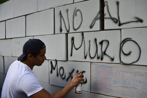 Pintadas sobre un muro hecho con cajas de cartón en contra del muro, en México .