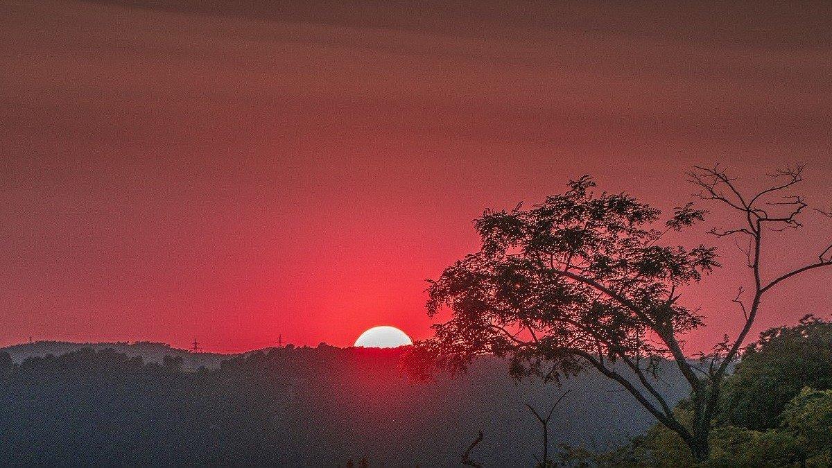 El sol poniéndose tras una montaña.