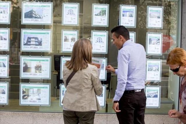 Una clienta y un comercial miran las ofertas de una inmobiliaria.
