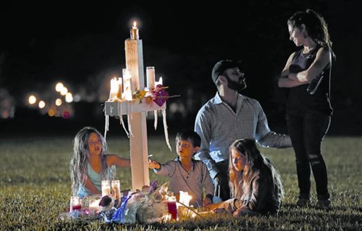 Una familia recuerda a una de las 17 víctimas de la matanza, ante el instituto de Parkland, en Florida.