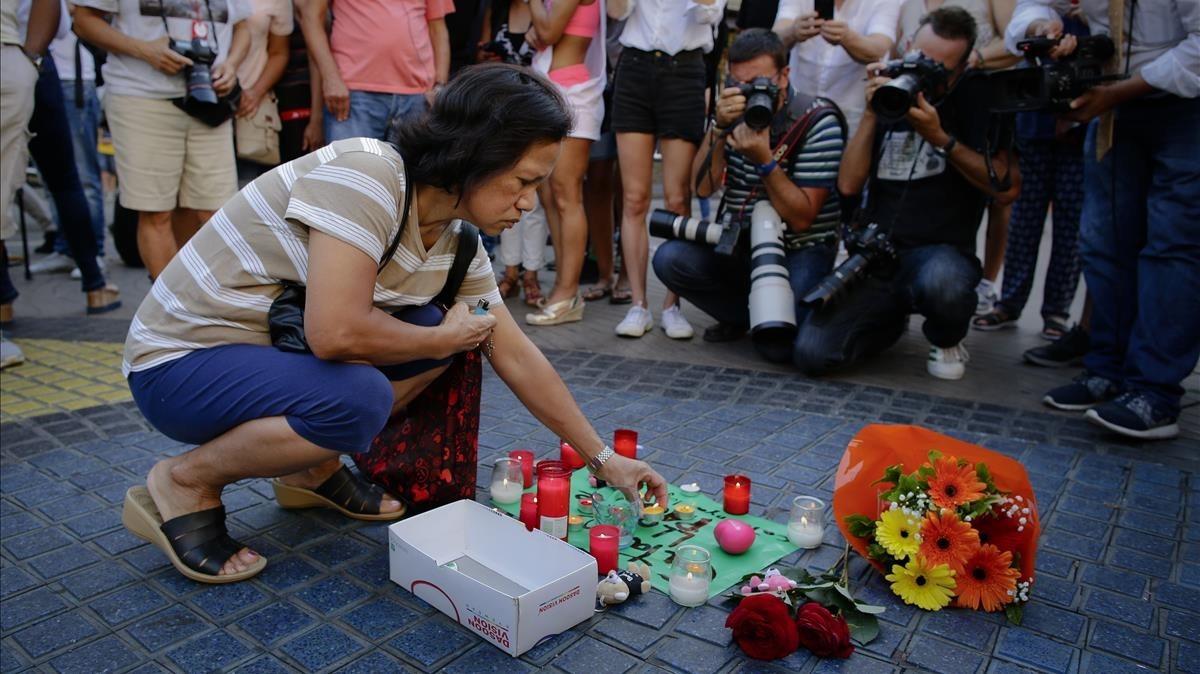 Una mujer deposita una vela sobre un cartel en el que puede leerse: Catalunya, lloc de pau, en la Rambla.