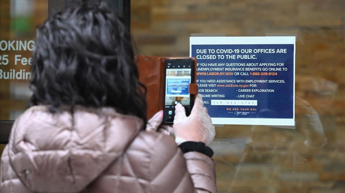 Una mujer toma una foto de un cartel colgado frente a una oficina del Departamento de Trabajo cerradapor coronavirus, este miércoles en Nueva York.