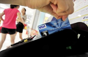 Una mujer usa su tarjeta de crédito.