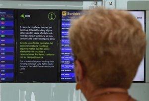 Una pasajera, ante una pantalla que informa de la huelga en el aeropuerto de El Prat.