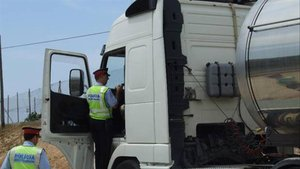 Una patrulla de los Mossos accede a la cabina de un camión en un control.