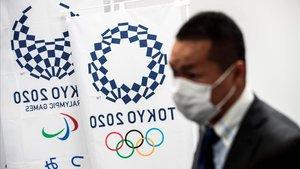 Una persona se protege con mascarilla delante de unas banderas con el logo de Tokio-2020