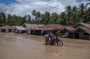 Unos jóvenes en motocicleta por una carretera inundada en Sumatra.
