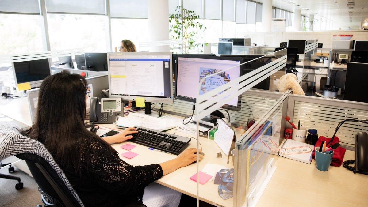 Una trabajadora delante de su ordenador, con mascarilla y pantalla protectora para evitar posibles contagios.