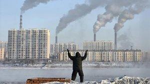 Un hombre hace ejercicio frente a unas chimeneas en el río Songhua, en Jilin (China), en el 2014.
