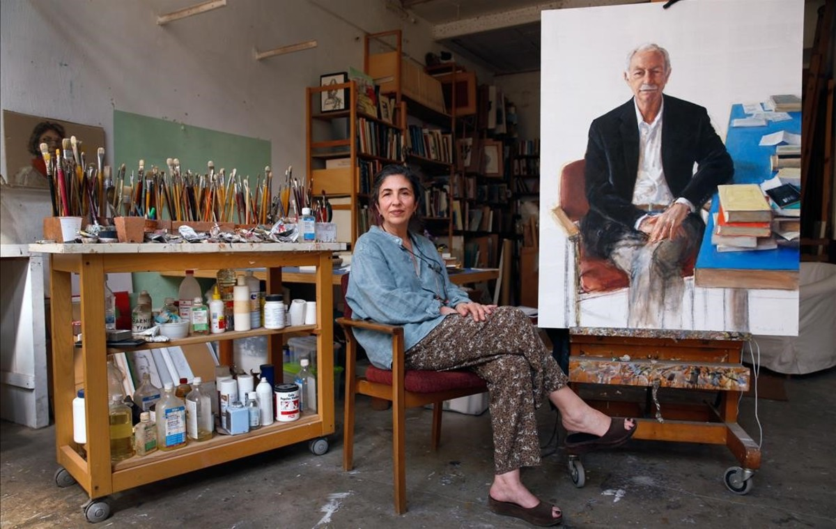 Leticia Feduchi posa junto al retrato de Eduardo Mendoza que ha realizado para la galería de los Premio Cervantes de la Biblioteca Nacional.
