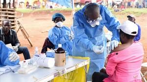 Un sanitario administra la vacuna contra el ébola a una mujer que tuvo contacto con un enfermo.