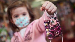 Una niña con mascarilla muestra una mascarilla, en Pamplona.