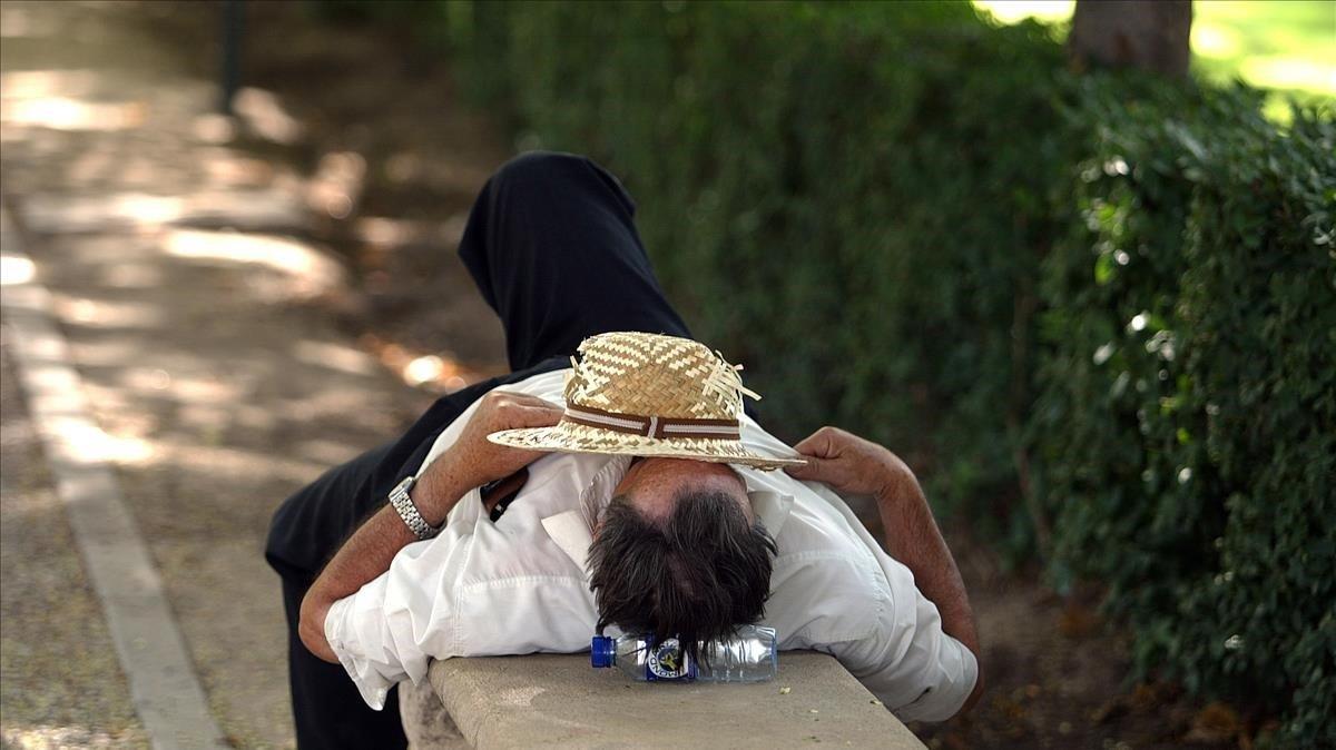Un hombre descansa en el parque del Retiro de Madrid
