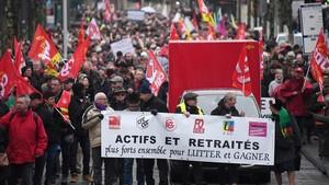 Manifestantes con una pancarta que alude a la lucha conjunta de jubilados y trabajadores, en Estrasburgo, el 15 de marzo.
