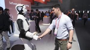 Un asistente saluda a un robot en el último Mobile World Congress.