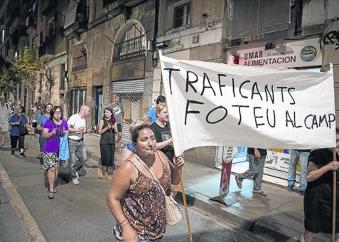 Cacerolada de los vecinos contra la presencia de traficantes en el Raval y miembros de la Guardia Urbana ante el número 18 de la calle de Sant Vicenç, donde han sido ocupados pisos.